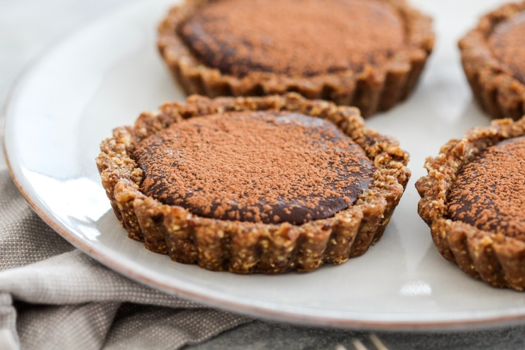 4 Mini Date and Walnut Tarts with a Chocolate Coconut Filling sitting on a white plate